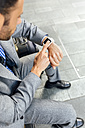 Close-up of businessman using his smartwatch in the city - MGOF03491