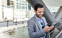 Smiling businessman looking at cell phone in the city - MGOF03494