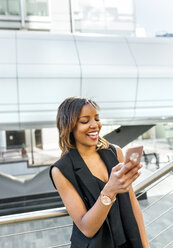 Smiling woman looking at her cell phone in the city - MGOF03500