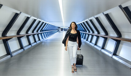 Businesswoman with suitcase walking through a tunnel - MGOF03506