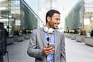 Smiling businessman with headphones and cell phone in the city - MGOF03515