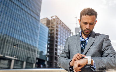 Businessman checking the time in the city - MGOF03521