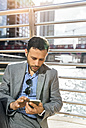 Businessman sending messages with his smartphone in the city - MGOF03527