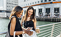 Two women on a bridge with takeaway coffee and cell phone - MGOF03530