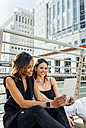 Two happy women sitting on a bridge sharing a tablet in the city - MGOF03536