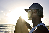 Man with surfboard watching sunset on the beach - ECPF00008