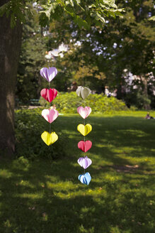 Heart-shaped garland made of paper hanging in garden - CMF00692