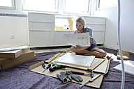 Woman reading assembly instructions at home - ECPF00010