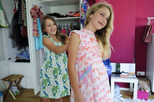 Two girls putting on dresses - ECPF00022