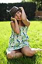 Happy playful girl wearing hat sitting in garden - ECPF00037