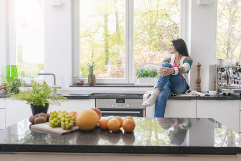 Smiling woman in kitchen looking out of window - JOSF01241