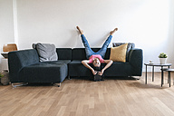 Woman at home with tablet lying on sofa upside down - JOSF01244