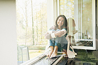 Portrait of smiling woman at home on windowsill - JOSF01253