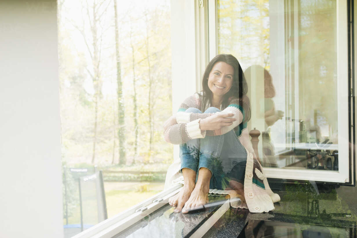 Portrait of smiling woman at home on windowsill - JOSF01253 - Joseffson/Westend61