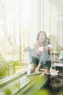Laughing woman at home sitting on windowsill - JOSF01256