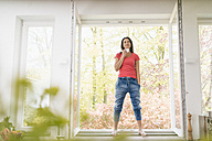 Smiling woman standing in kitchen on windowsill - JOSF01259