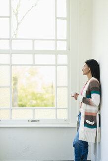 Woman at home looking out of window - JOSF01265