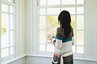 Woman at home looking out of window - JOSF01268