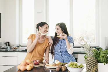 Two happy women in kitchen preparing fruit - JOSF01274