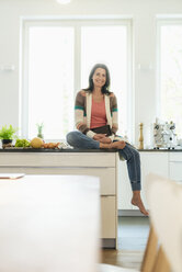 Portrait of smiling woman at home sitting on kitchen counter - JOSF01289
