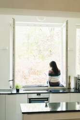 Woman in kitchen sitting on windowsill - JOSF01292
