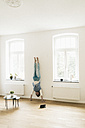 Woman at home doing a handstand at the wall - JOSF01298