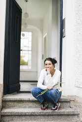 Woman with flowers sitting on doorstep - JOSF01310