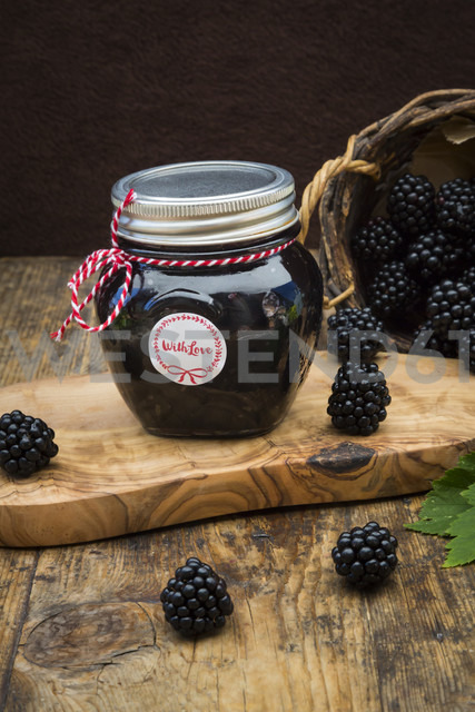 Glass of homemade blackberry jelly and blackberries on wood - LVF06273
