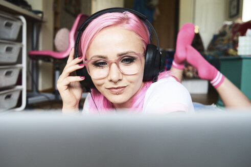 Young woman with pink hair listening to music via laptop at home - IGGF00060