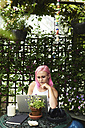 Young woman with pink hair using laptop in cozy garden - IGGF00072