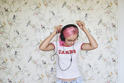 Enthusiastic young woman with pink hair listening to music at home - IGGF00078