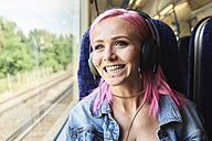 Happy young woman with pink hair listening to music while traveling by train - IGGF00081