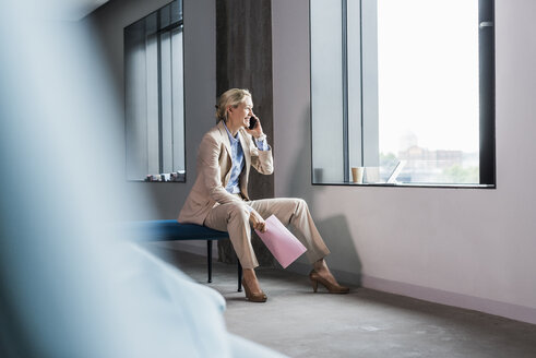 Smiling businesswoman on the phone sitting at the window - UUF11395