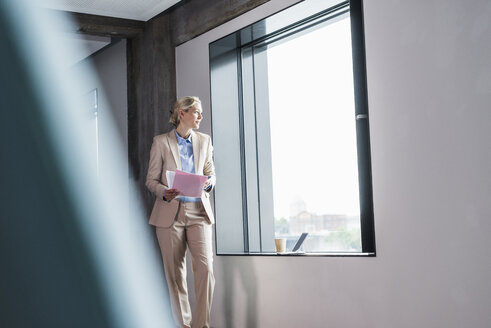 Businesswoman standing at the window holding document - UUF11398