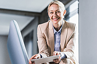 Portrait of smiling businesswoman holding tablet - UUF11401