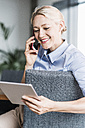 Smiling businesswoman on the phone holding tablet - UUF11410