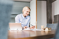 Smiling businesswoman working at desk in office - UUF11413