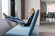 Businesswoman sitting on couch with feet up using tablet - UUF11422