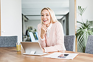 Smiling businesswoman with tablet in office - UUF11443