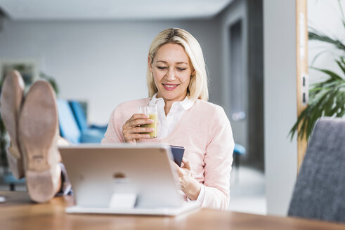 Businesswoman holding smoothie and using cell phone in office - UUF11449
