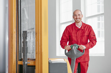 Portrait of smiling man in factory with forklift - RHF02026