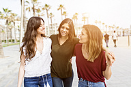 Three happy female friends strolling on the boardwalk - GIOF03001
