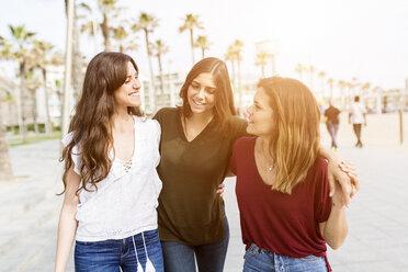 Three happy female friends strolling on the boardwalk - GIOF03001