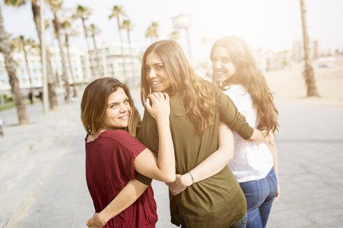 Three happy female friends strolling on the boardwalk - GIOF03004