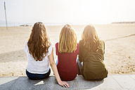 Rear view of three female friends sitting at the beach - GIOF03007