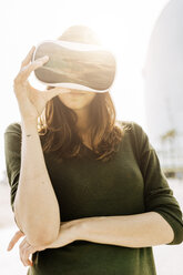 Young woman wearing VR glasses outdoors - GIOF03010