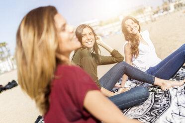 Three happy female friends sitting on the beach - GIOF03013