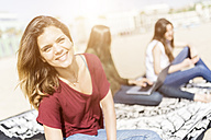 Portrait of smiling young woman on the beach with friends in background - GIOF03022