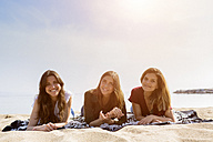 Portrait of three female friends relaxing on the beach - GIOF03028