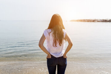 Rear view of young woman standing at the sea - GIOF03031